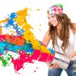 Woman splashing colorful paint — Stock Photo