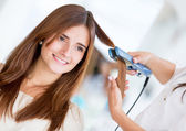 Using a hair straightener at the salon — Stock Photo