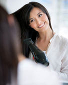Woman blow drying her hair — Stock Photo