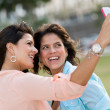 Girls taking a picture with the phone — Stockfoto