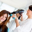 Stylist blow drying hair — Stock Photo