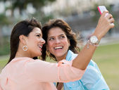 Girls taking a picture with the phone — Stock Photo