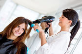 Stylist blow drying hair — Stok fotoğraf