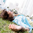 Pensive woman lying at the park — Stock Photo