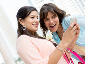 Girls using a smart phone — Stock Photo