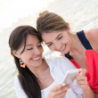 Stock Photo: Women using app on cell phone