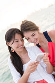 Women using an app on a cell phone — Stok fotoğraf