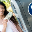 Stock Photo: Woman paying for parking in cash