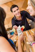 Friends paying for drinks at the bar — Stockfoto