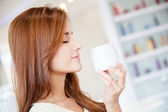 Woman holding moisturizing cream — Stock Photo
