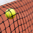 Tennis ball bouncing on the net - Stock Photo