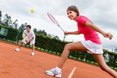Woman playing doubles in tennis — Stok fotoğraf