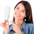 Stockfoto: Womwith energy saving lightbulb