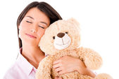Woman daydreaming with a teddy bear — Stock Photo