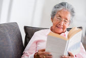 Elder woman reading a book — Stockfoto