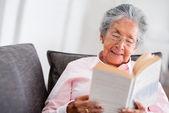 Starší žena čte knihu — Stock fotografie