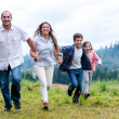 Happy family running outdoors - Stock Photo