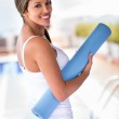 Woman with a yoga mat — Stock Photo #26480449