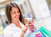 Woman using cell phone while shopping — Foto Stock