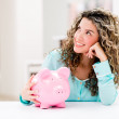 Stock Photo: Thoughtful womwith piggybank
