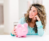 Thoughtful woman with a piggybank — Stock Photo