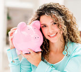 Happy woman with a piggybank — Stock Photo