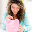Stock Photo: Womputting savings in piggybank