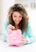 Woman putting savings in a piggybank — Stock Photo