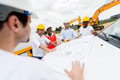 Group of architects looking at blueprints — Stock Photo