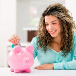 Stock Photo: Happy womsaving money