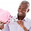 Stock Photo: Mtaking money from piggybank