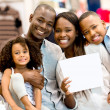 Family with a banner at a store — Stock Photo