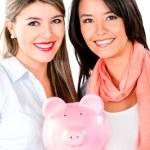 Women keeping savings in a piggybank — Stock Photo #30974131