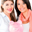 Stock Photo: Women keeping savings in piggybank