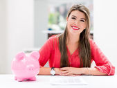 Woman saving in a piggybank — Stock Photo