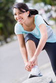 Female runner tying her shoelace — Stock Photo