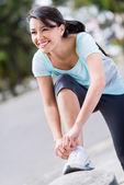 Female runner tying her shoelace — Stock Photo
