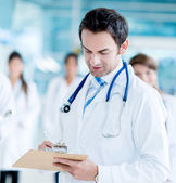 Doctor writing medical history — Stock Photo