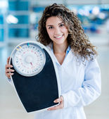 Doctor holding a weight scale — Stock Photo