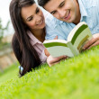 Couple reading outdoors — ストック写真