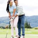 Man teaching woman to play golf — Stock Photo