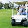 Couple in a golf cart — Stock Photo