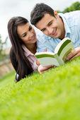 Couple reading outdoors — Stock Photo