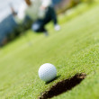 Stock Photo: Golf ball going into a hole