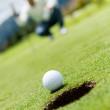 Гольф мяч вдаваясь в отверстие — Стоковое фото