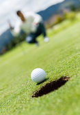 Golf ball going into a hole — Stock fotografie