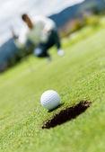 走进一个洞的高尔夫球场球 — 图库照片