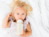 Girl drinking a baby bottle — Stock Photo