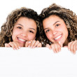 Twin sisters holding banner — Stock Photo