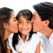 Parents kissing their daughter — Stockfoto